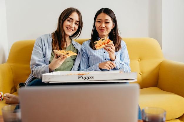 Ragazze allegre mangiando pizza e guardando commedia Foto Gratuite