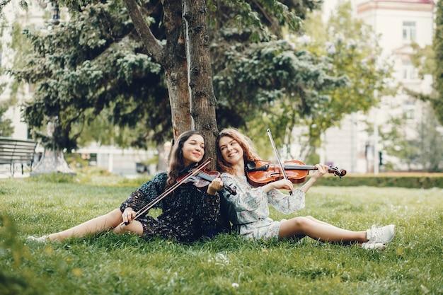 Ragazze belle e romantiche in un parco con un violino Foto Gratuite
