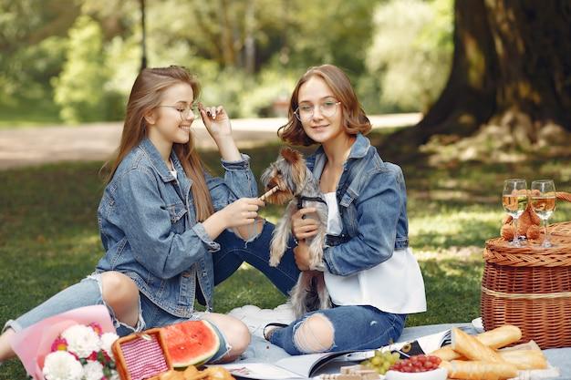 Ragazze carine in un parco giocando con cagnolino Foto Gratuite