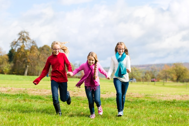 Ragazze che attraversano il parco autunno o autunno Foto Premium