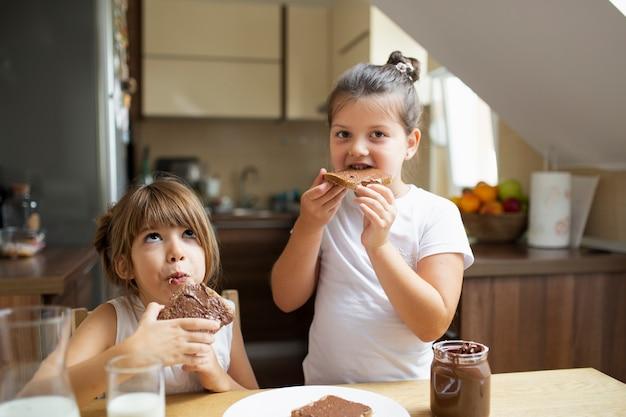 Ragazze che mangiano prima colazione di mattina a casa Foto Gratuite