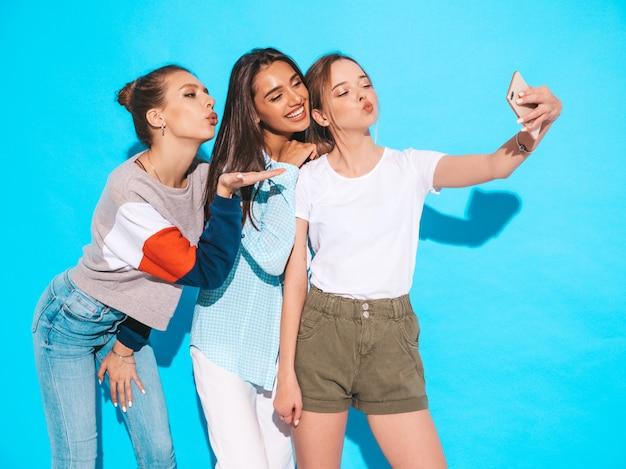 Ragazze che prendono le foto dell'autoritratto del selfie sullo smartphone modelli che posano vicino alla parete blu in studio femmina che mostra le emozioni positive danno bacio dell'aria Foto Gratuite