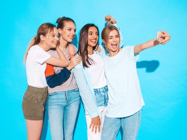 Ragazze che prendono le foto dell'autoritratto del selfie sullo smartphone modelli che posano vicino alla parete blu in studio, femmina che mostra le emozioni positive del fronte Foto Gratuite