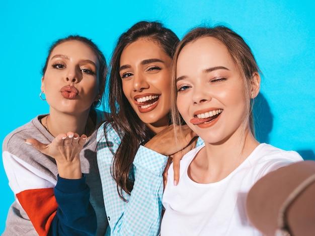 Ragazze che prendono le foto dell'autoritratto del selfie sullo smartphone modelli che posano vicino alla parete blu in studio. Foto Gratuite