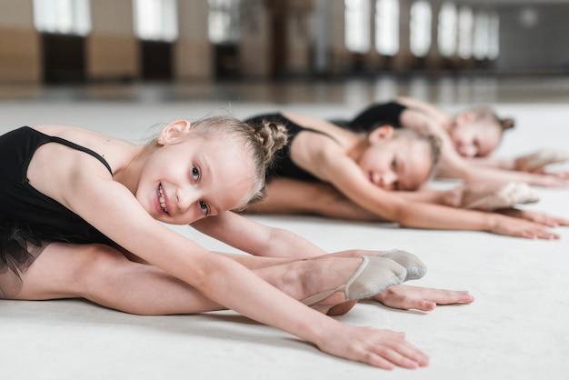 Ragazze che si allungano in avanti con i suoi amici prima di ballare in studio Foto Gratuite