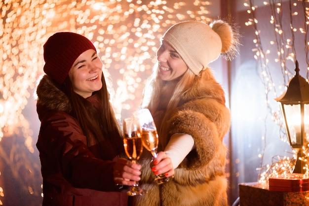 Ragazze che si godono lo champagne. ritratto all'aperto delle signore su sfondo chiaro. Foto Premium