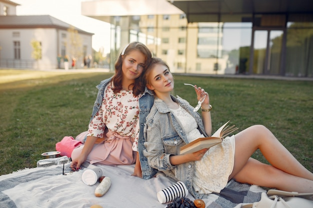 Ragazze che si siedono su una coperta in un parco di estate Foto Gratuite