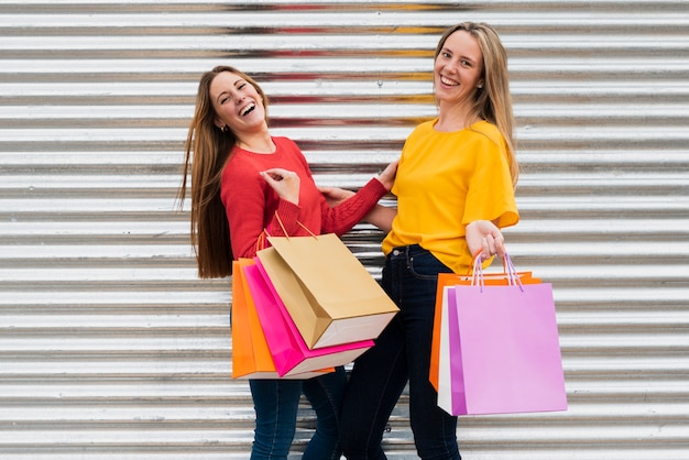 Ragazze con borse della spesa guardando la fotocamera Foto Gratuite