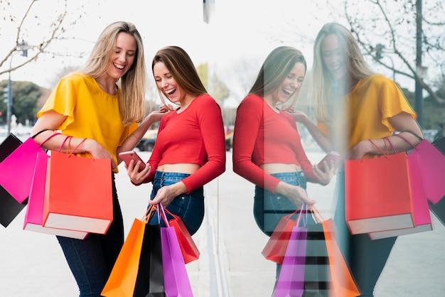 Ragazze con i sacchetti della spesa che esaminano telefono vicino alla finestra Foto Gratuite