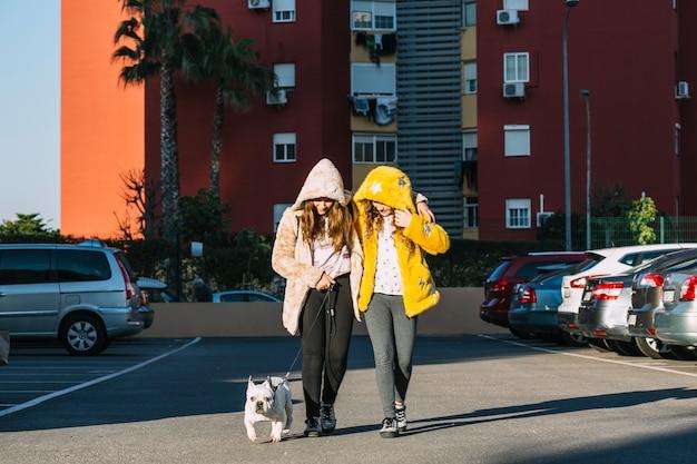 Ragazze con il cane che cammina sul parcheggio Foto Gratuite