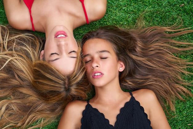 Ragazze degli migliori amici dell'adolescente che si trovano giù su tappeto erboso Foto Premium