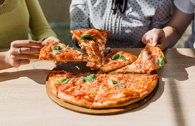 Ragazze del primo piano con pizza al ristorante Foto Gratuite
