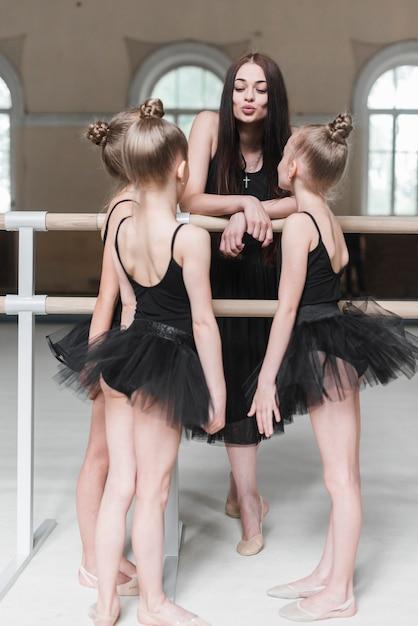 Ragazze della ballerina che esaminano istruttore femminile che tiene il broncio vicino alla sbarra Foto Gratuite