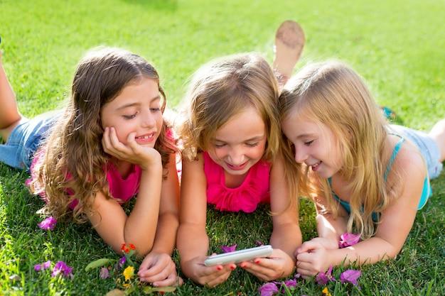 Ragazze di amici dei bambini che giocano a internet con smartphone Foto Premium