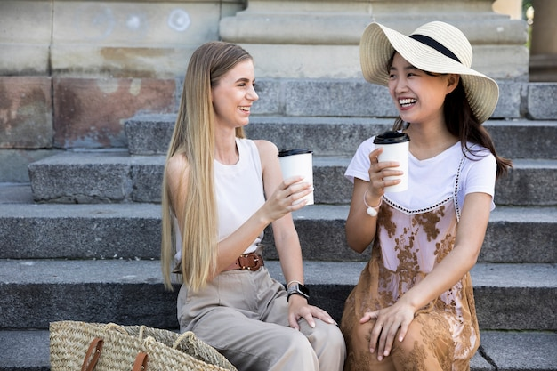 Ragazze di vista frontale che hanno una tazza di caffè Foto Gratuite