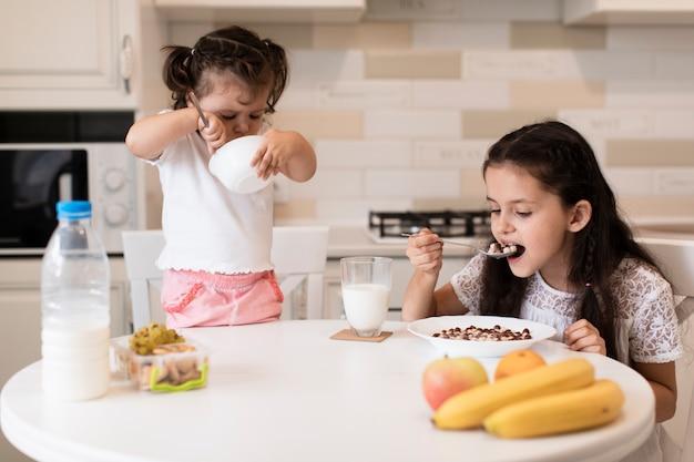 Ragazze di vista frontale che mangiano prima colazione Foto Gratuite