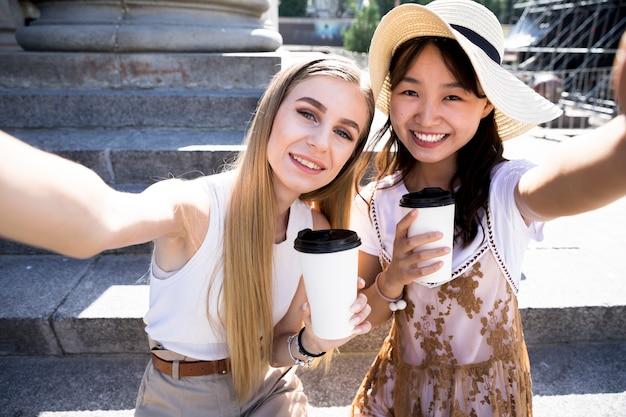 Ragazze di vista frontale prendendo un selfie Foto Gratuite