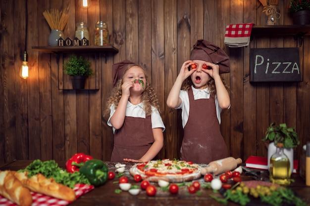 Ragazze divertenti che cucinano pizza e che imbrogliano con i pomodori e la lattuga Foto Premium