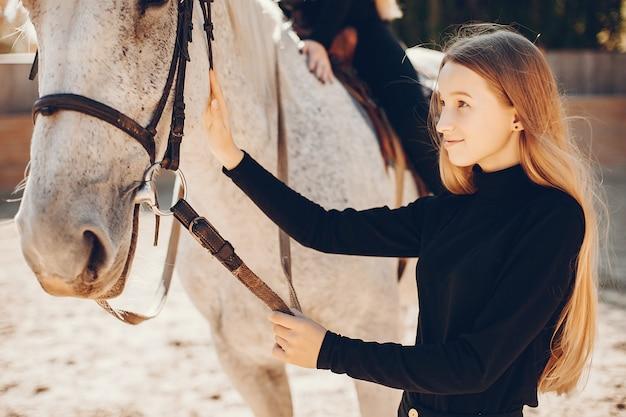 Ragazze eleganti con un cavallo in un ranch Foto Gratuite