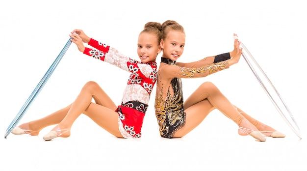 Ragazze gemelle che fanno esercizi di ginnastica con i cerchi. Foto Premium