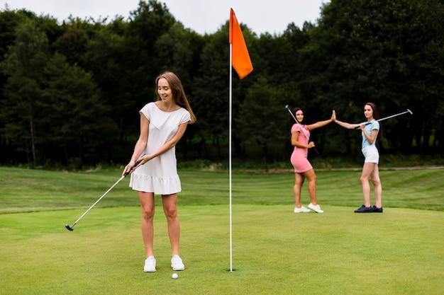 Ragazze graziose della foto a figura intera che giocano a golf Foto Gratuite