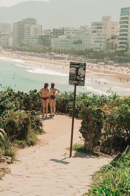 Ragazze in bikini in piedi e guardando la spiaggia di rio de janeiro Foto Gratuite