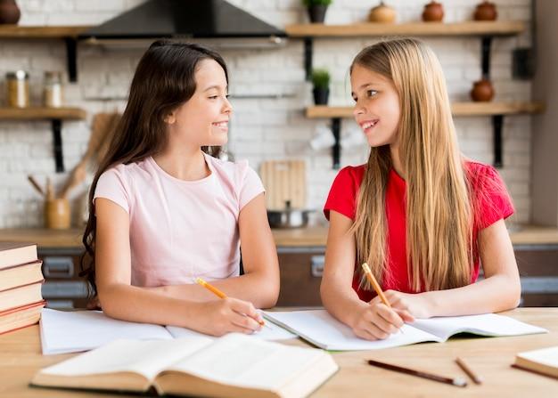 Ragazze positive che scrivono insieme nei quaderni Foto Gratuite