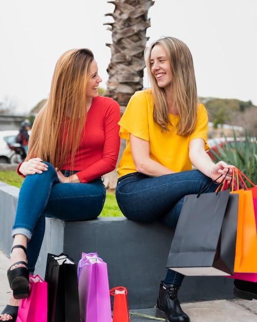 Ragazze sorridenti con i sacchetti della spesa che se lo esaminano Foto Gratuite