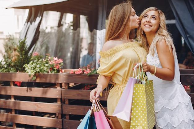Ragazze sveglie con il sacchetto della spesa in una città Foto Gratuite
