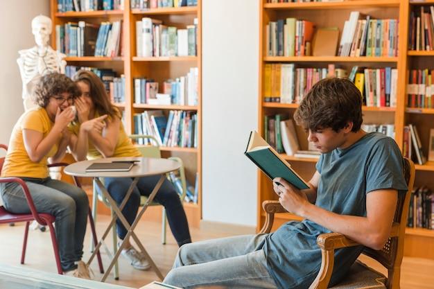 Ragazze teenager che spettegolano sulla lettura del compagno di classe Foto Gratuite