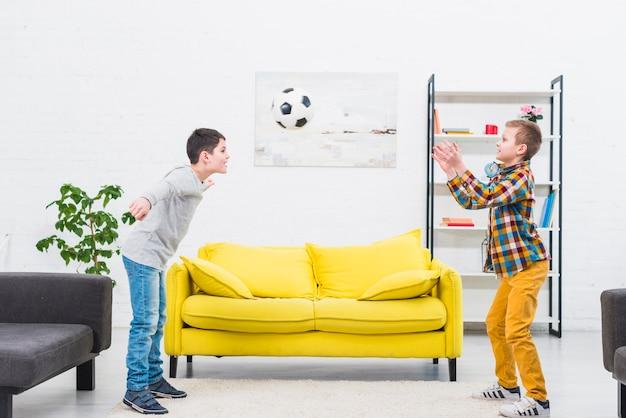 Ragazzi che giocano a calcio nel salotto Foto Gratuite