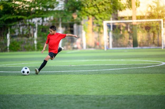 Ragazzi che giocano a calcio sul campo di pratica del calcio Foto Premium