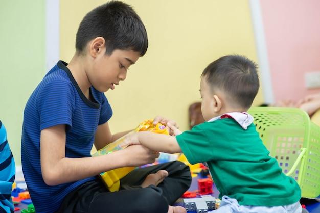 Ragazzini che giocano insieme giocattolo nella stanza Foto Premium