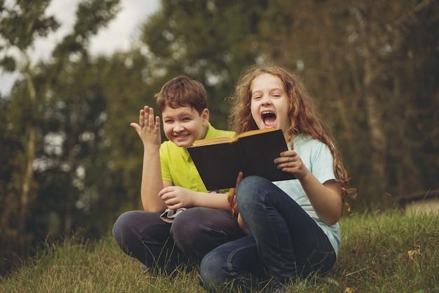 Ragazzini che leggono il libro all'aperto. concetto di educazione. Foto Premium
