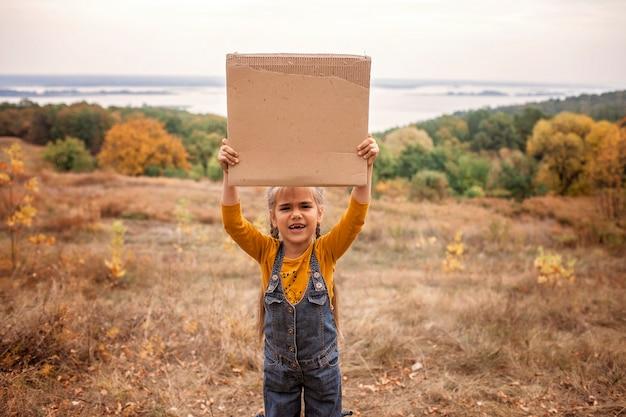 Ragazzini che tengono un manifesto sopra la natura di autunno Foto Premium
