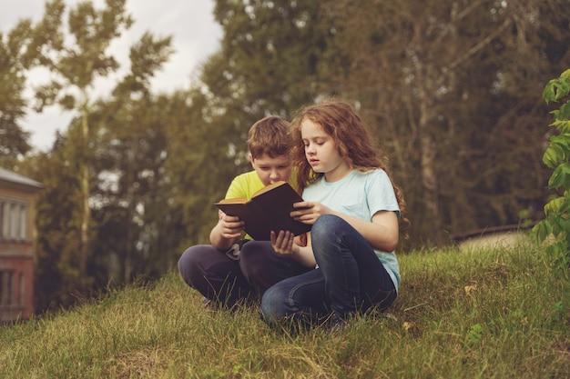 Ragazzini intelligenti che leggono il libro all'aperto. Foto Premium