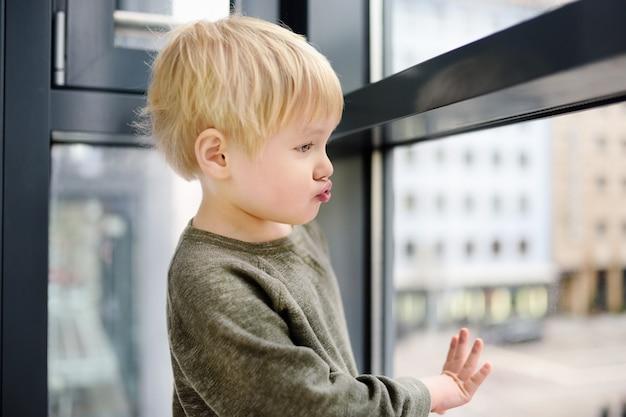 Ragazzino adorabile che si siede sulla finestra vicino alla finestra panoramica e guardando fuori Foto Premium