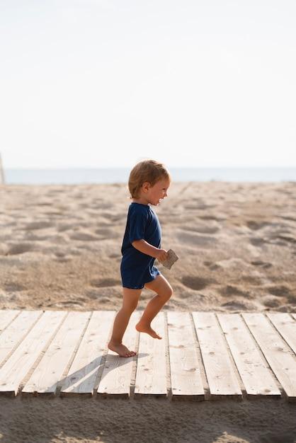 Ragazzino allegro che funziona alla spiaggia Foto Gratuite