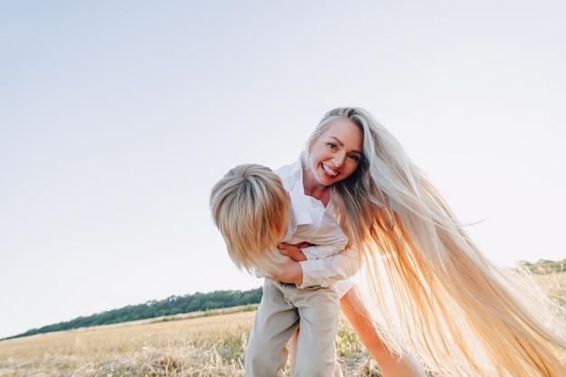 Ragazzino biondo che gioca con la mamma con capelli bianchi con fieno nel campo. estate, tempo soleggiato, agricoltura. infanzia felice. Foto Gratuite