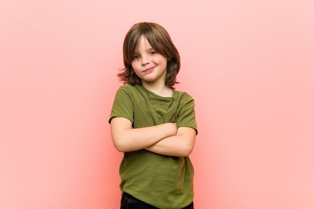Ragazzino che aggrotta le sopracciglia per il dispiacere, tiene le braccia conserte Foto Premium