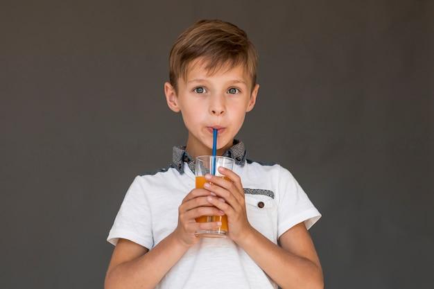 Ragazzino che beve il succo di arancia Foto Gratuite