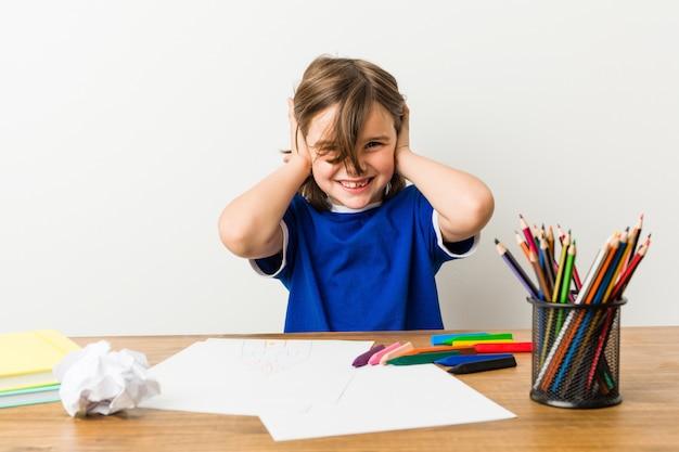 Ragazzino che dipinge e che fa i compiti sulla sua scrivania che copre le orecchie con le mani. Foto Premium