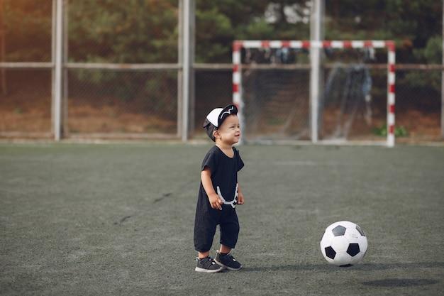 Ragazzino che gioca a calcio in un campo sportivo Foto Gratuite