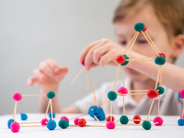 Ragazzino che gioca con il gioco di chimica Foto Gratuite