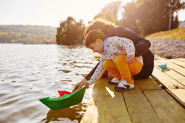 Ragazzino che gioca con la nave di carta giocattolo sul lago Foto Gratuite
