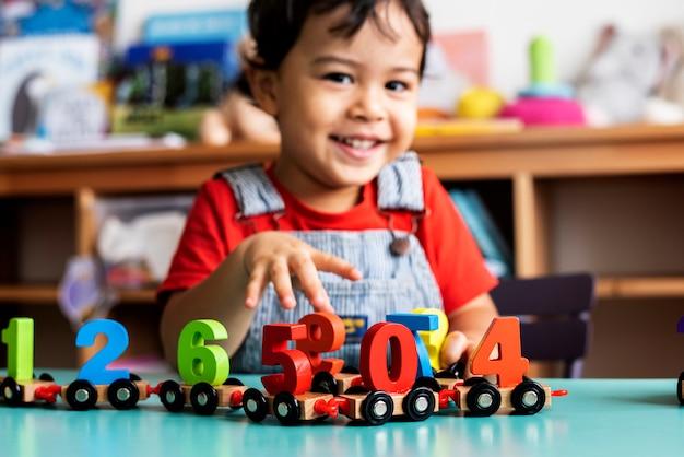Ragazzino che gioca giocattolo di legno di matematica alla scuola materna Foto Premium