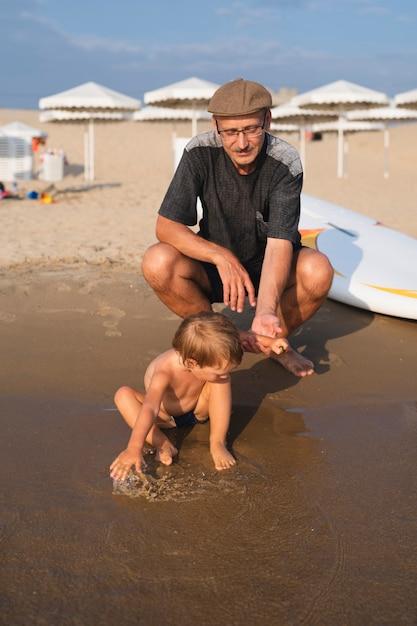 Ragazzino che gioca in acqua con il nonno accanto Foto Gratuite