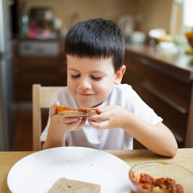 Ragazzino che mangia spuntino a casa Foto Gratuite