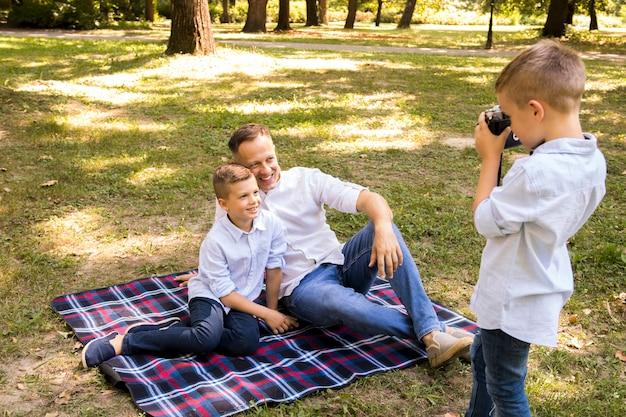 Ragazzino che prende una foto di suo fratello e suo padre Foto Gratuite