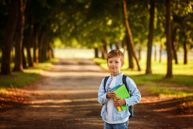 Ragazzino che torna a scuola. bambino con zaino e libri. Foto Premium
